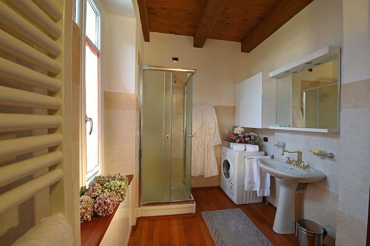 Vista del bagno completo di lavatricee stendino