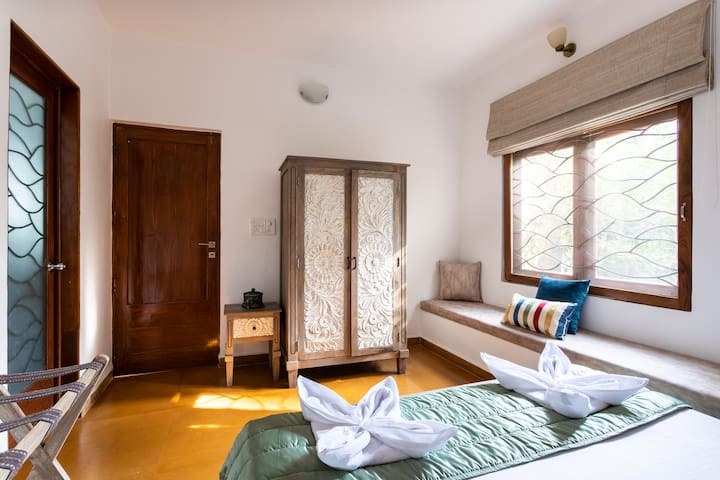 The First Bedroom is located on the Ground floor with a cupboard, Airconditioner, and En-suite bathroom.  To the Right of the bed is a Sitting area near the Window