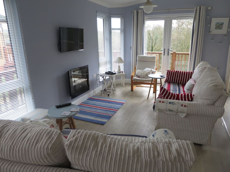 Nautical themed lounge with two relaxing sofas . Television with Freeview and electric fire  Two radiators . Double patio doors.