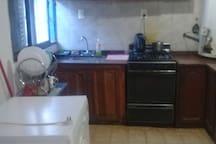 Cocina equipada con horno, heladera, y lavarropas.