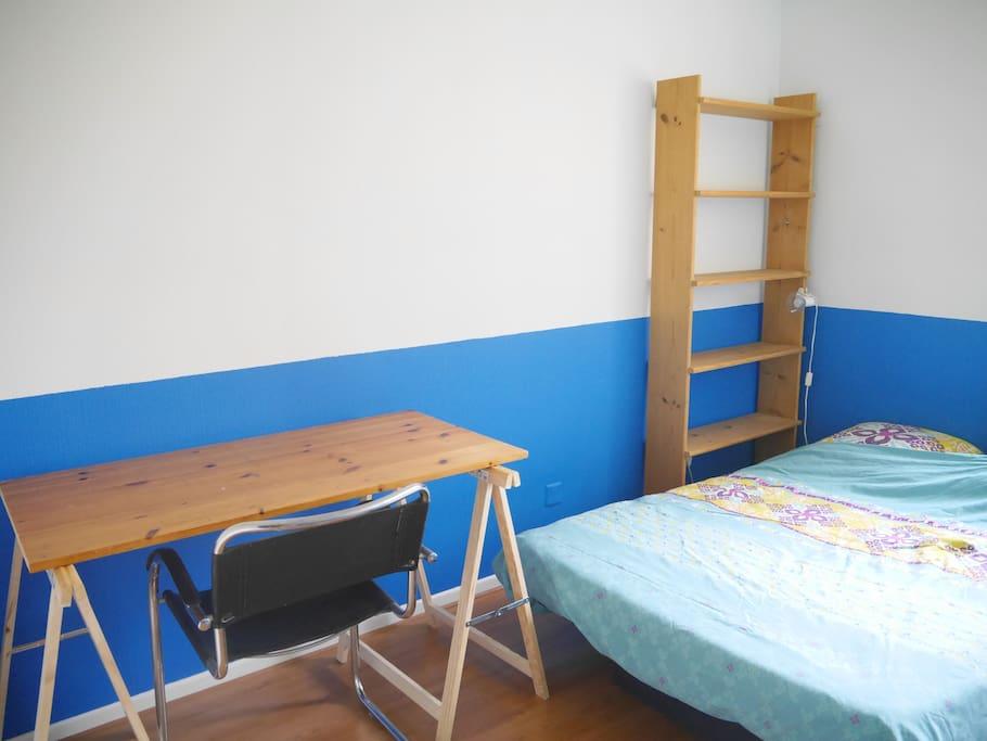 chambre équipée d'un lit double, d'un bureau, d'une étagère et d'un placard