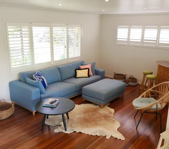Living room with wooden floors, and louvered windows for cooling breezes overlooking the gardens. Recently furnished with beautiful, new pieces from local and Australian artisans, which give the house a relaxed and chic beach vibe.