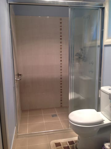 New bathroom with spacious shower recess and multiple water pressure shower head.