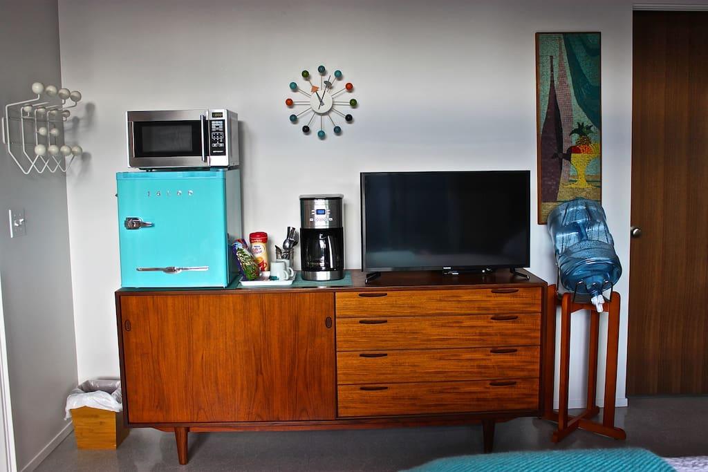 Mini fridge, coffee maker, microwave, flat screen TV, water.