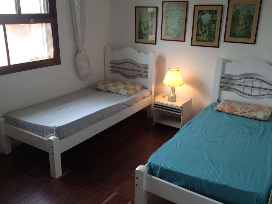 Quarto branco, 2 camas de solteiro.