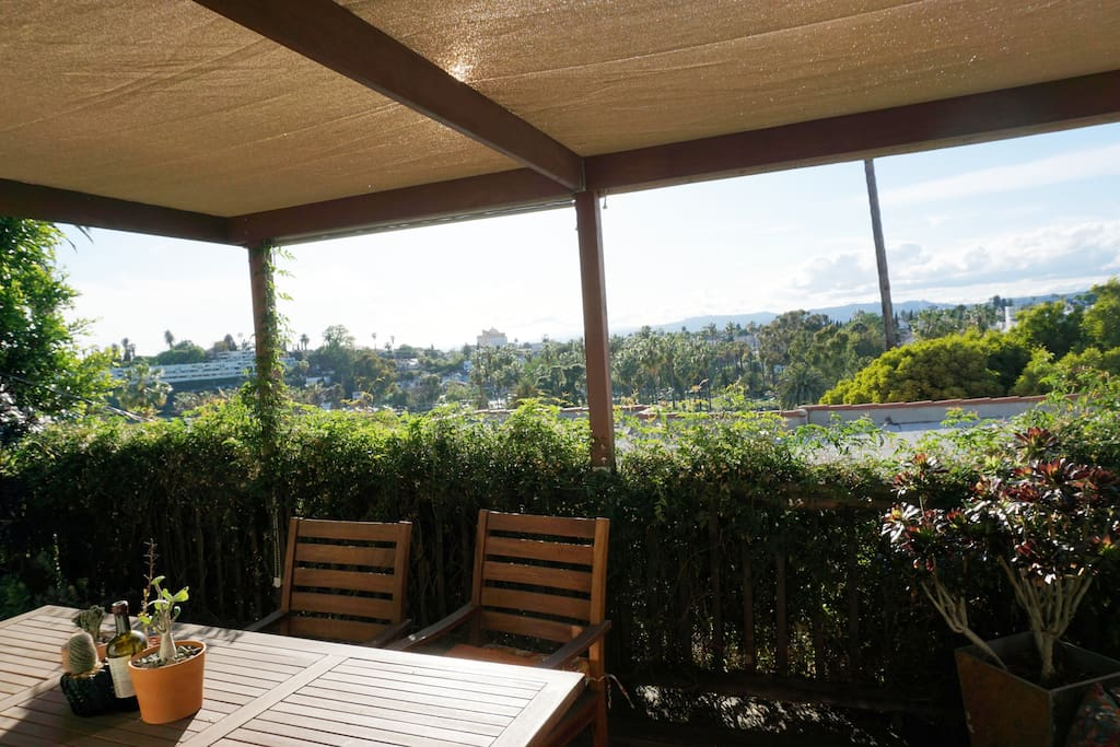 Spacious redwood deck just off the living room. It has a Westerly view looking over Echo Park Lake. Half is covered with a beautiful pergola for shade. There are numerous potted plants and a teak dining table set.