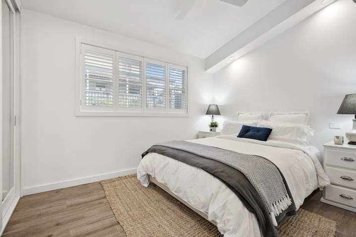 Bedroom with comfortable queen size bed, fresh white linen, fluffy light duvet, selection of pillows including memory foam. Built in robe with shelves, drawers and hanging space and Plantation shutters to complete the luxurious feel.