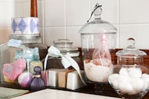Lovely soaps,  bathbombs, Rose & Lavender bath salts  displayed in glass apothecary jars set on vintage oak bath stand