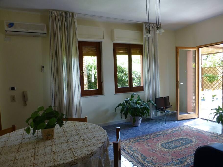 soggiorno con porta d'accesso al giardino privato