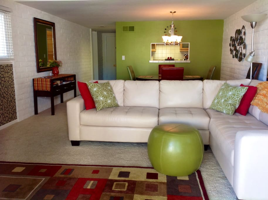 Living room decorated in modern retro colors with roomy  leather sectional. Large flat screen TV and wifi. Large solid wood table in dining area with passthrough to galley kitchen.