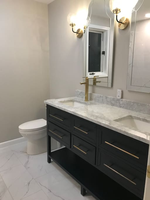 Bathroom with double sink, heated floors and Bluetooth speakers.