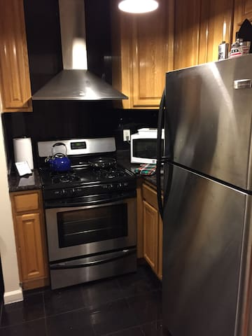 Kitchen with huge fridge, microwave, toaster oven, and gas stove with exhaust hood.