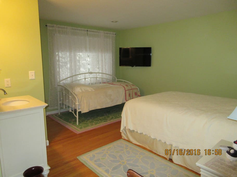 Room 2 - large room with a queen bed & day bed, private bath with claw foot tub & shower, looking out into a wooded surround.
