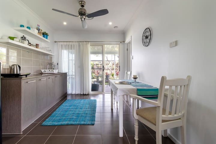 The large private kitchenette area with dining table, which leads onto your patio area, has plenty of space to move around as you prepare your meals.