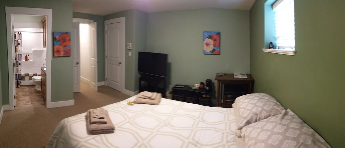 Primary Guest Bedroom; Large screen TV with full cable and Netflix.   Table and snack prep nook also in photo.
