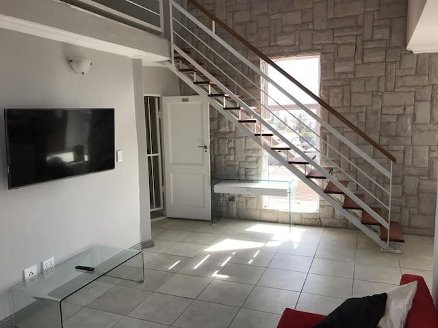 The entrance and 55 inch UHD Smart TV which uses the free Fibre connected WiFi is adjacent to the staircase to the main room and study area upstairs.