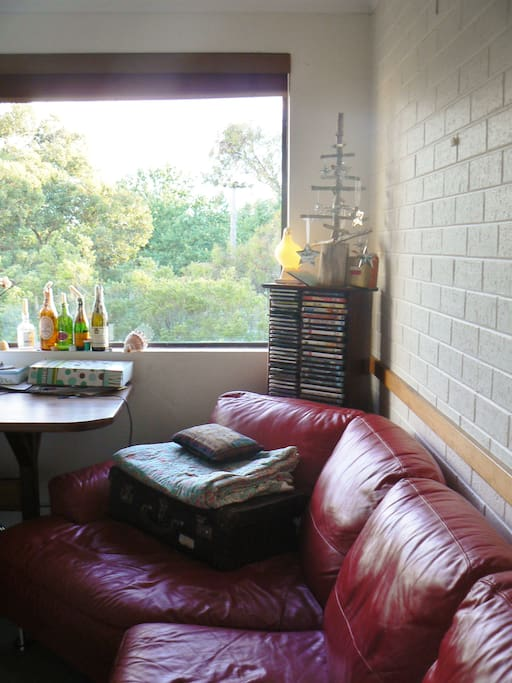 Relax on a comfortable leather sofa at tree height in a leafy suburb