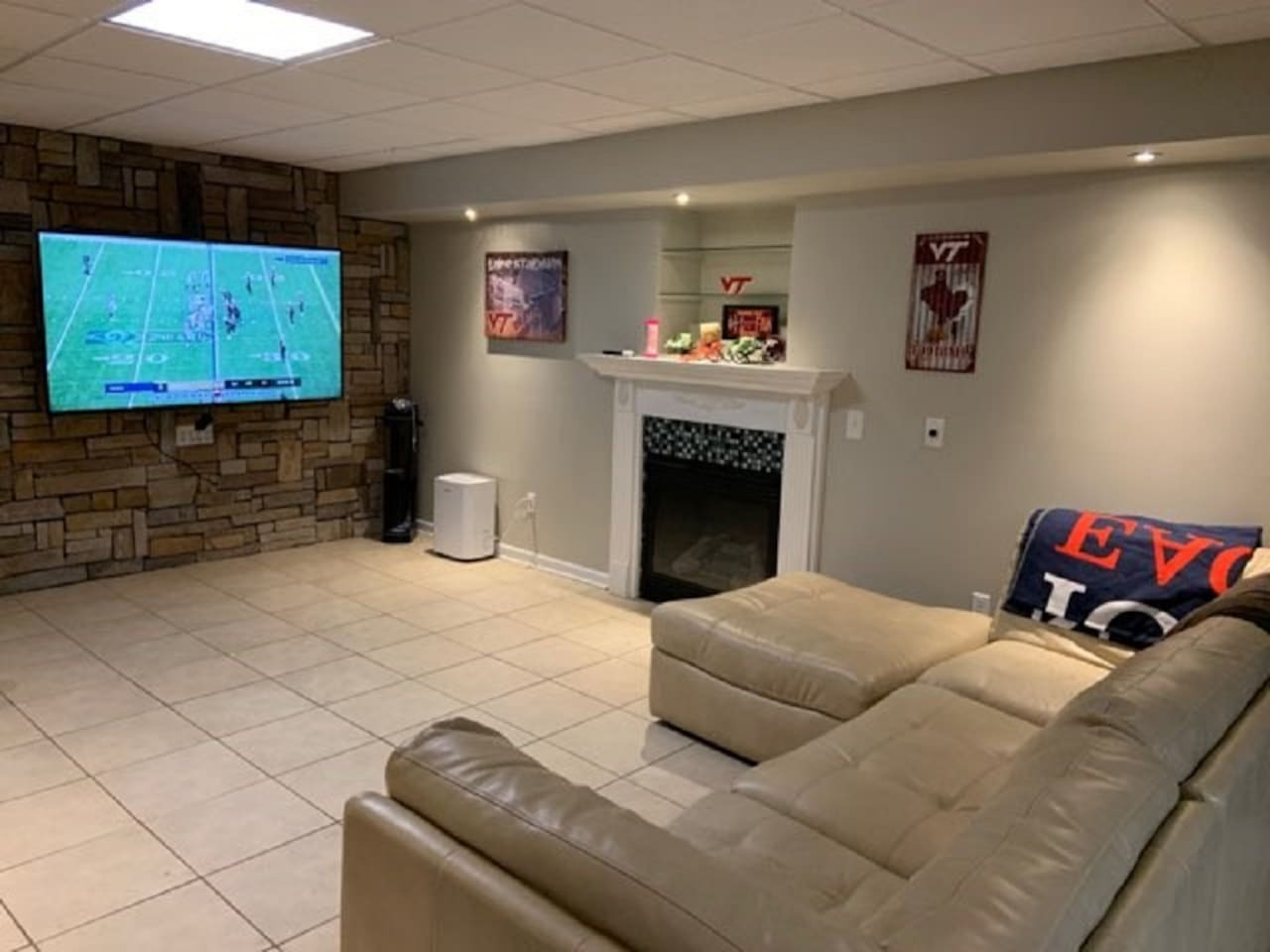 """Living room area with 70"""" TV and gas log fire place"""