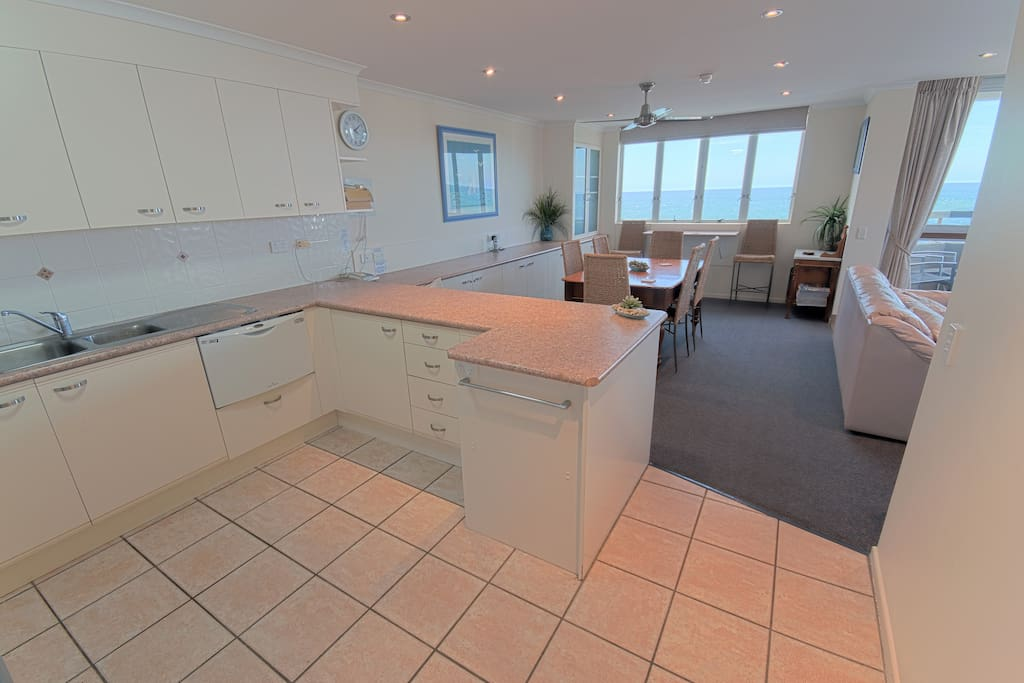Large kitchen leading to an open plan dining, living and outdoor balcony.