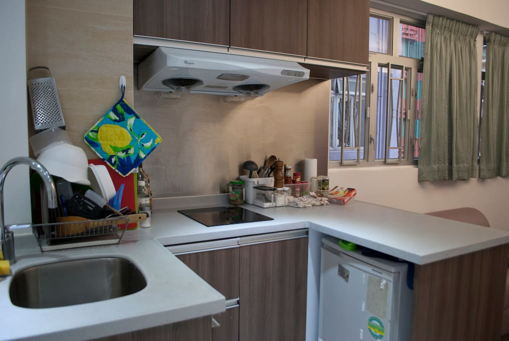 Kitchen features an induction cooker, a variety of cooking tools, and a good amount of preparation space.