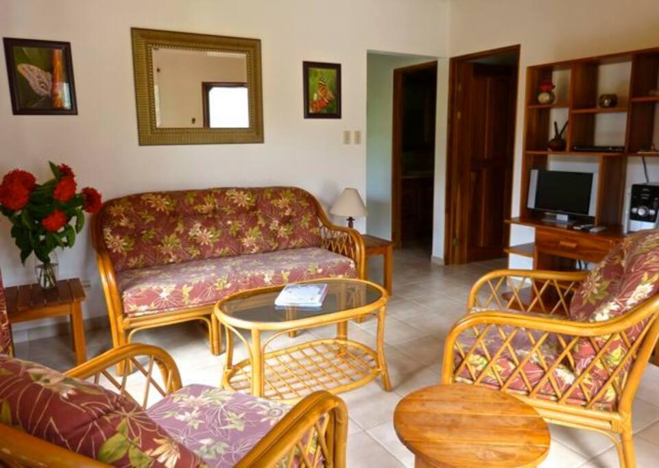 Salon lumineux avec meubles en rotin et en teck