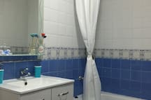 Salle de bain commune avec basque, baignoire et wc.