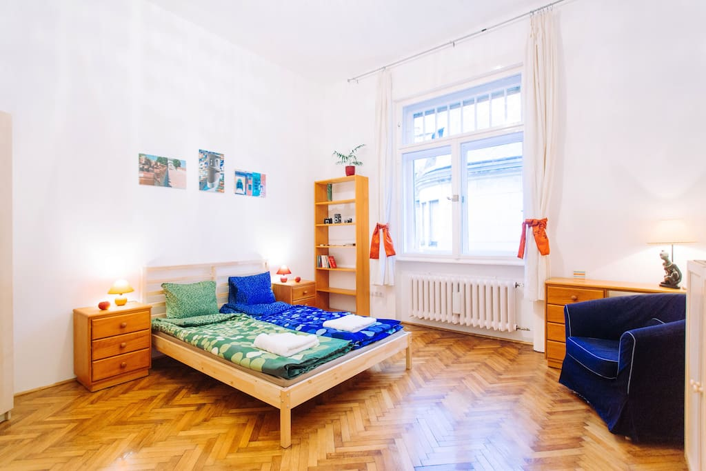 Bright bedroom with double bed in a quiet street