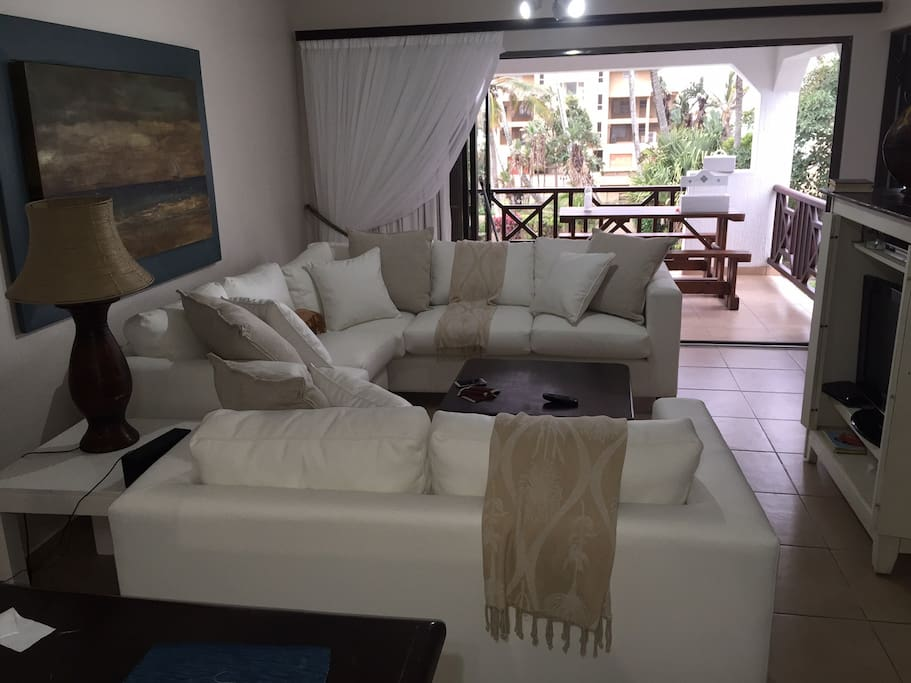 Open plan lounge, dining room, kitchen with stacker doors to patio, sea view.