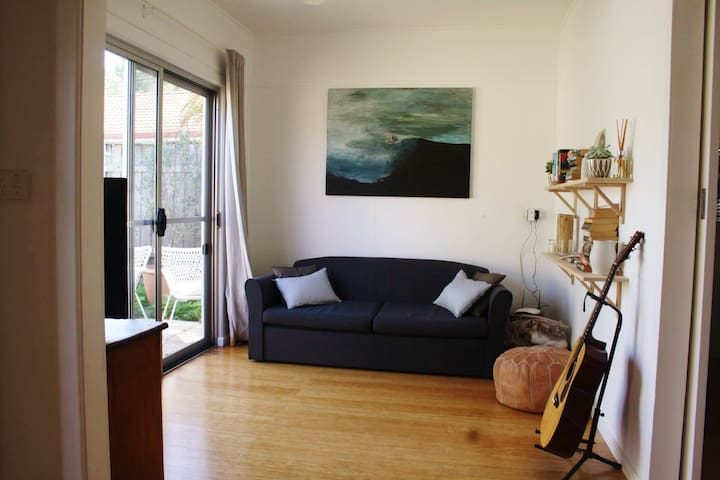 Living room with sofa bed and large sliding doors onto private courtyard