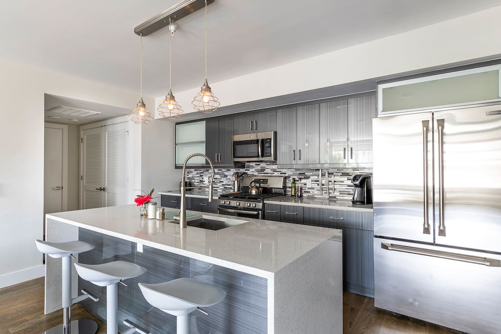 But, the designer kitchen may tempt you to stay in and cook. There's room for everybody at the dining table and additional seating on sculpted bar stools at the kitchen island.