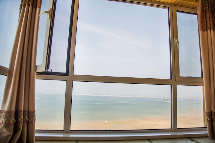 山海广场阳光纯海景大床房公寓有厨房房间内有榻榻米坐在床上看大海万科海港城专业物业管理