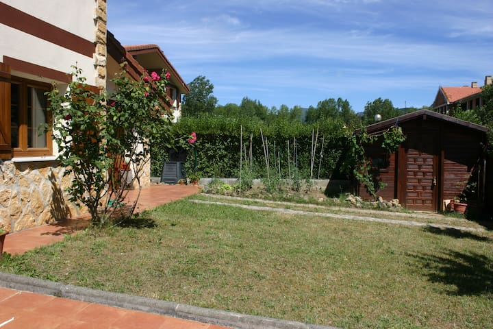 Parte del jardín delantero con vista de la pequeña huerta y cabaña para aperos y utensilios.