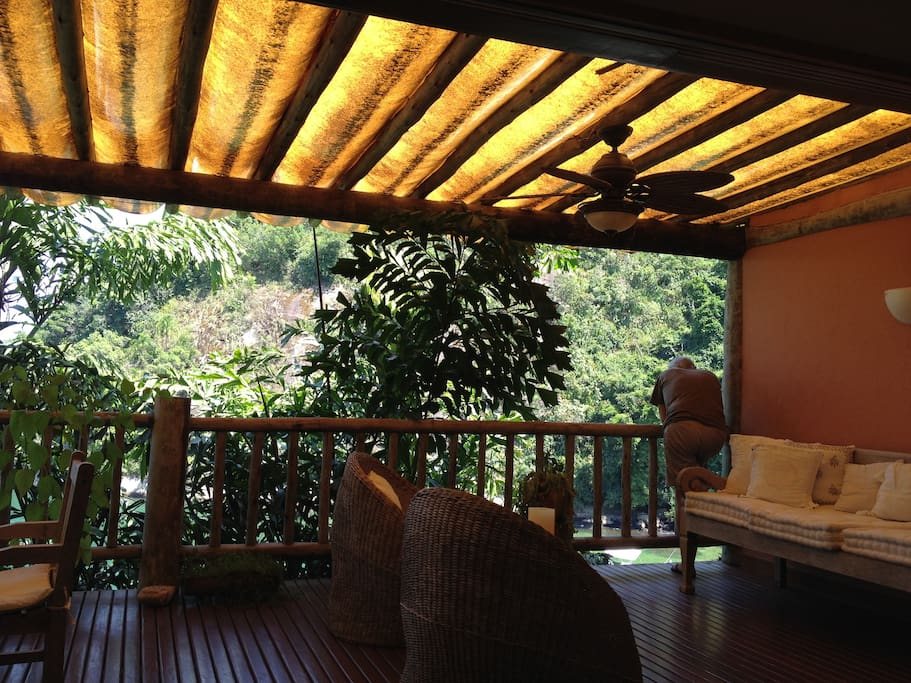 Verandah extending from living room area, with relaxing Bali lounger and chairs