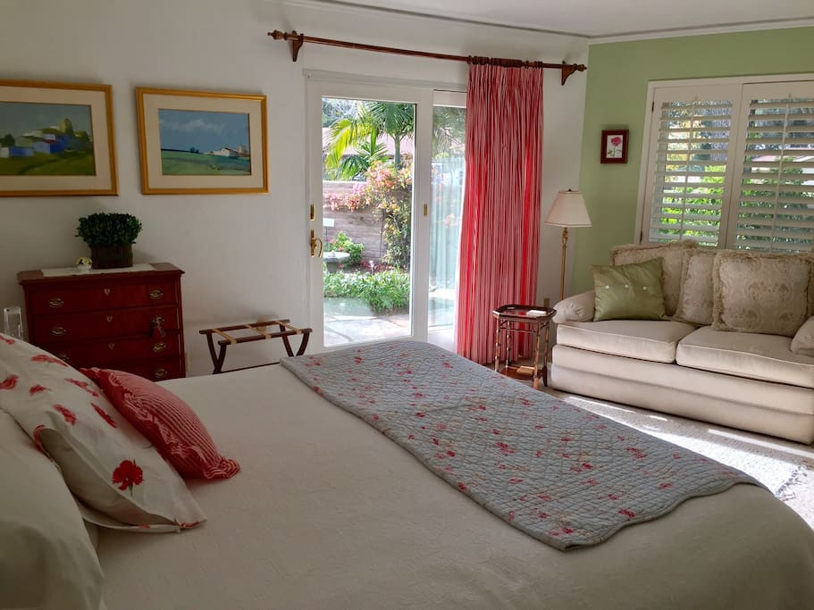 Bedroom with king bed that opens on to patio with trickling fountain and seasonal garden.