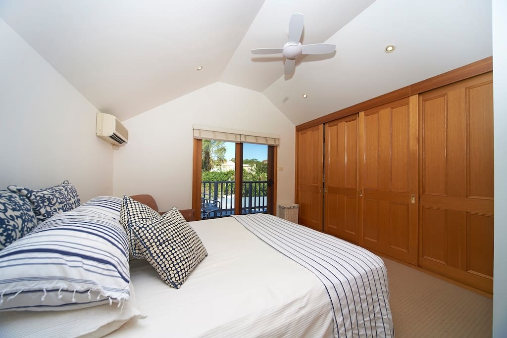 Master bedroom on upper level with ceiling fan, air conditioning, built in robes.  Port-a-cot available on request