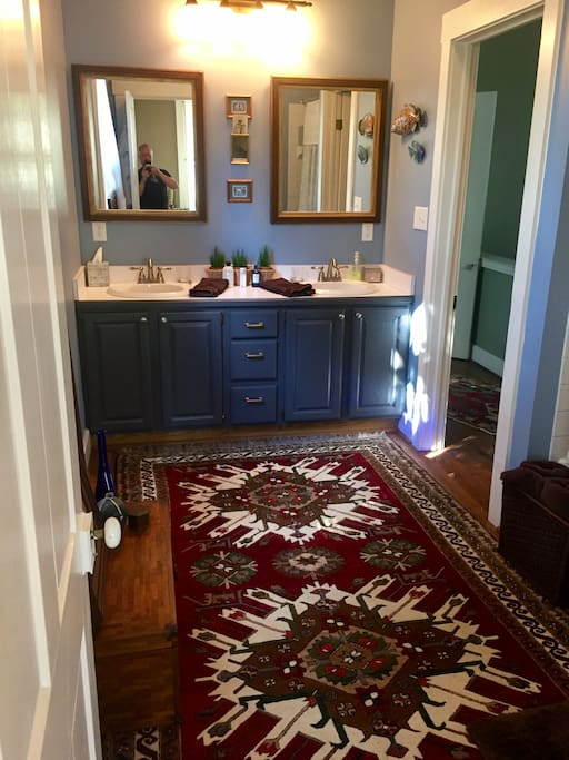 Large ensuite bath with double-sink vanity, imported Turkish rug, spa robes, and Keurig coffee-maker with coffee pods
