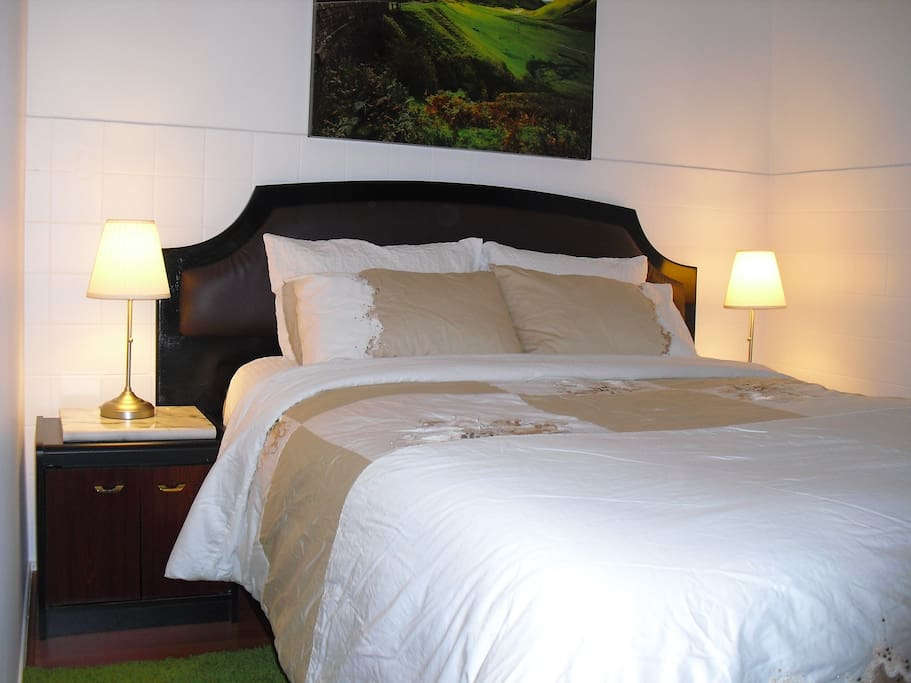 Perfectly glowing bed side lamps and beautifully painted artwork creates an inviting and comfortable bedroom atmosphere
