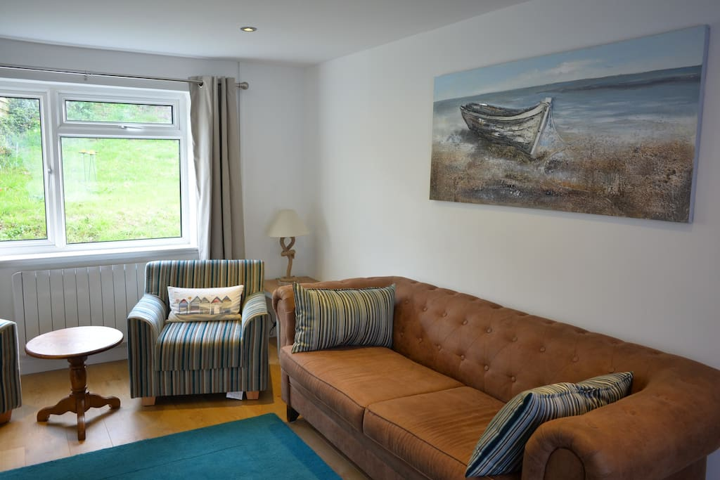 Living room with a 3 seater leather sofa, 2 easy chairs, and a swivelling reclining armchair.
