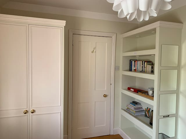 The room has a wardrobe, bookshelf and a small desk.