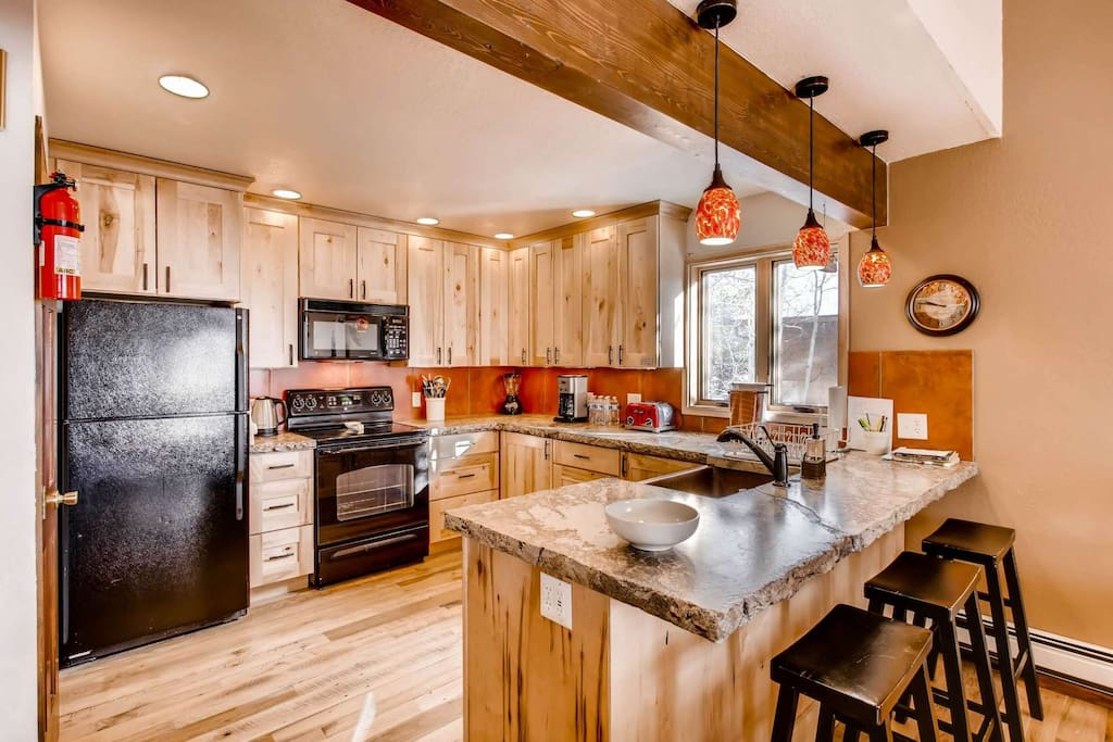 Updated Kitchen Features Stone Countertops and Deep Copper Sink