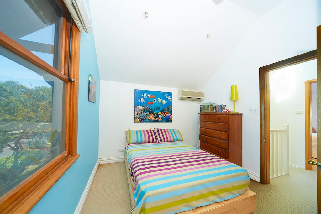 Double bedroom on upper level with built in robes, air conditioning and ceiling fan.