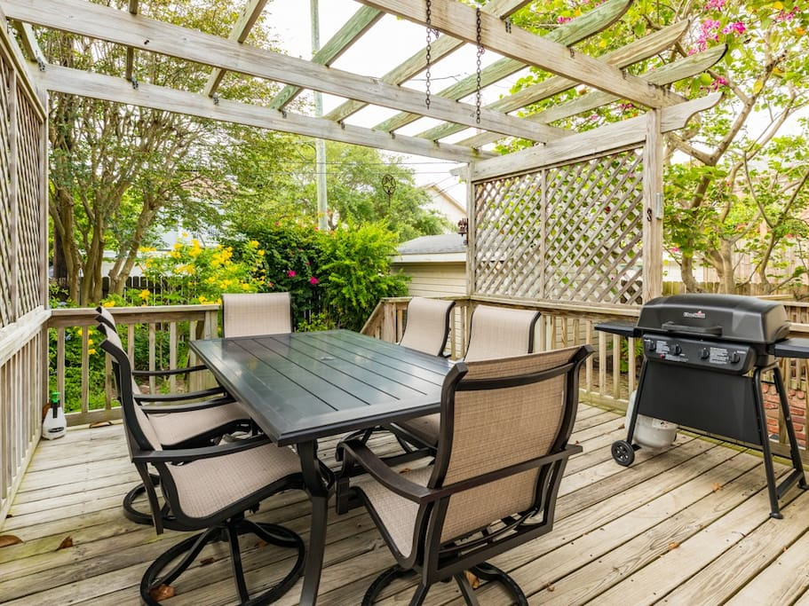 Outdoor seating and a grill on the deck accompanied by ample shade from the pergola and trees.