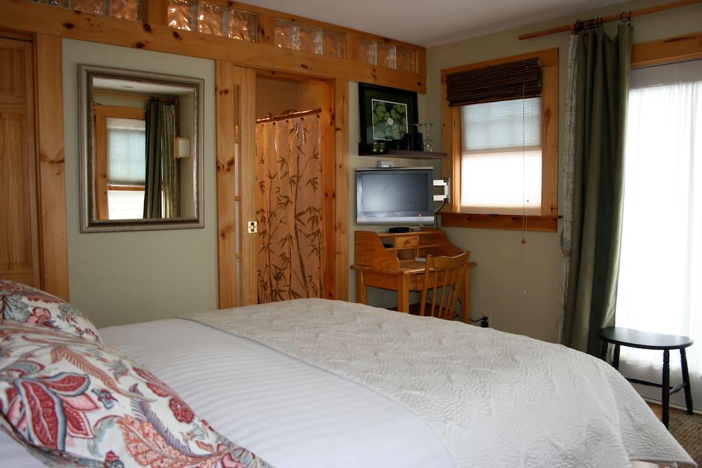 Closet, bath, flat screen cable TV, small desk, patio doors that open out to Garden.