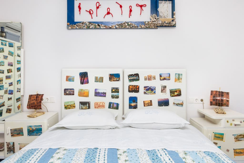 double bed with postcards and Kon-Tiki lamps on side