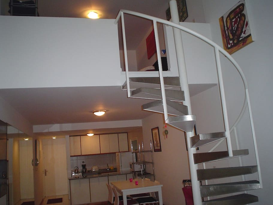 Spiral staircase to sleeping area. Kitchen and mirrored wall.