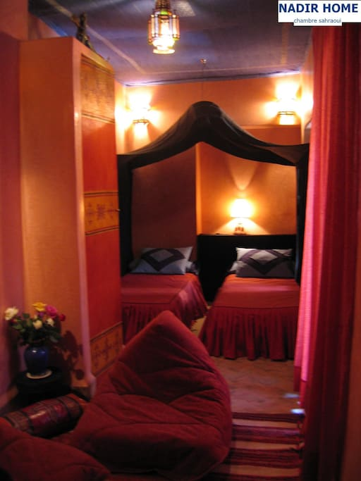 """Sous un voile de tente, la chambre """"sahraoui"""" accueille 2 personnes en lits simples (salle de bain avec douche, cheminée, petit salon, climatisation)"""