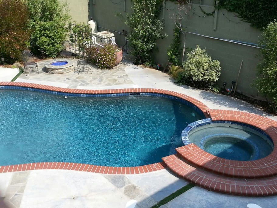 Swimming pool and jacuzzi in backyard