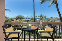 Private Lanai with seating for two amidst a view of the ocean off in the distance.