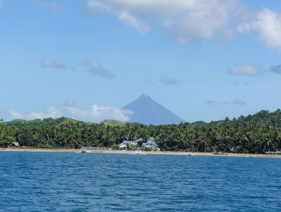 We are seaside, with a majestic view of the Mayon volcano in the background.