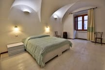 Spacious double bedroom with white wooden floors and empty barrel :)